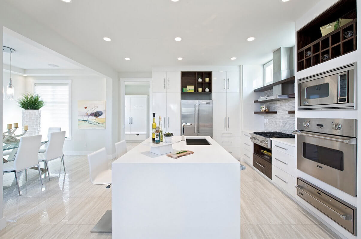 To add individuality and contrast to this all white kitchen space, stainless steel appliances and dark wood upper cabinets are used. Luxury kitchen hardwood flooring provides the final touch to a warm and cozy setting