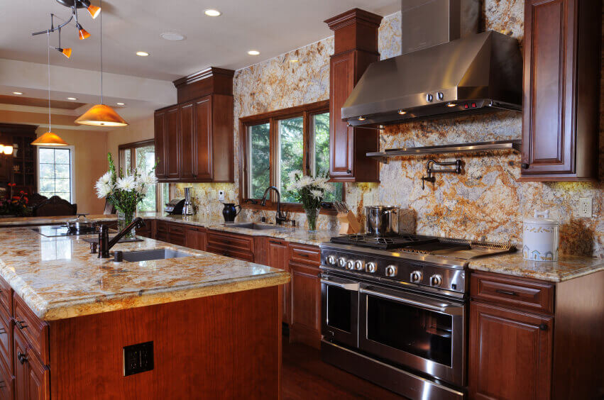 The smooth marble modern kitchen backsplash tile behind the stainless steel cooktop lightens the back wall for a secondary texture and color combination. It accents the hardwood floors and cabinets