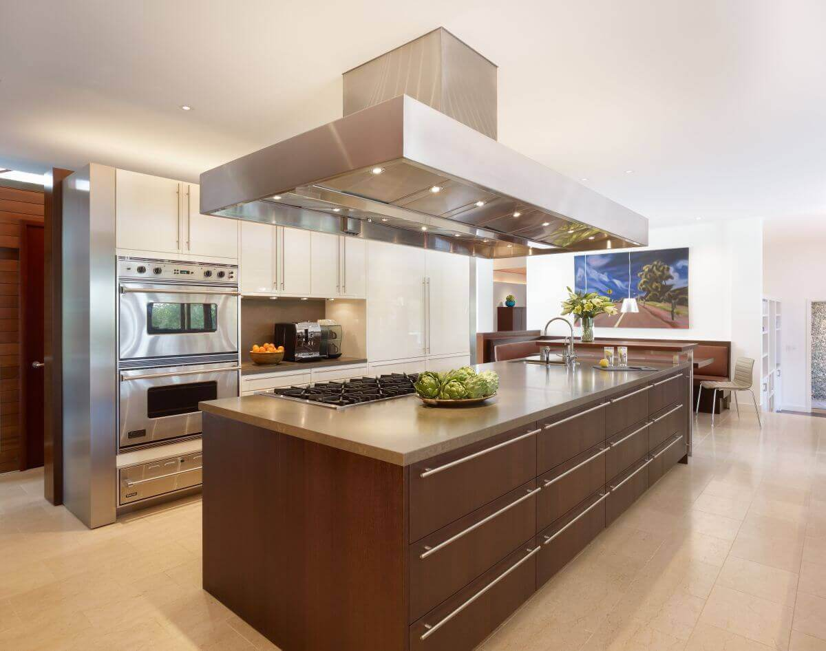 At first the look of this modern kitchen designs photo gallery evokes memories of a high school class, but the stainless steel appliances, wall art and bowl of fruits bring just enough of a color scheme to brighten the space