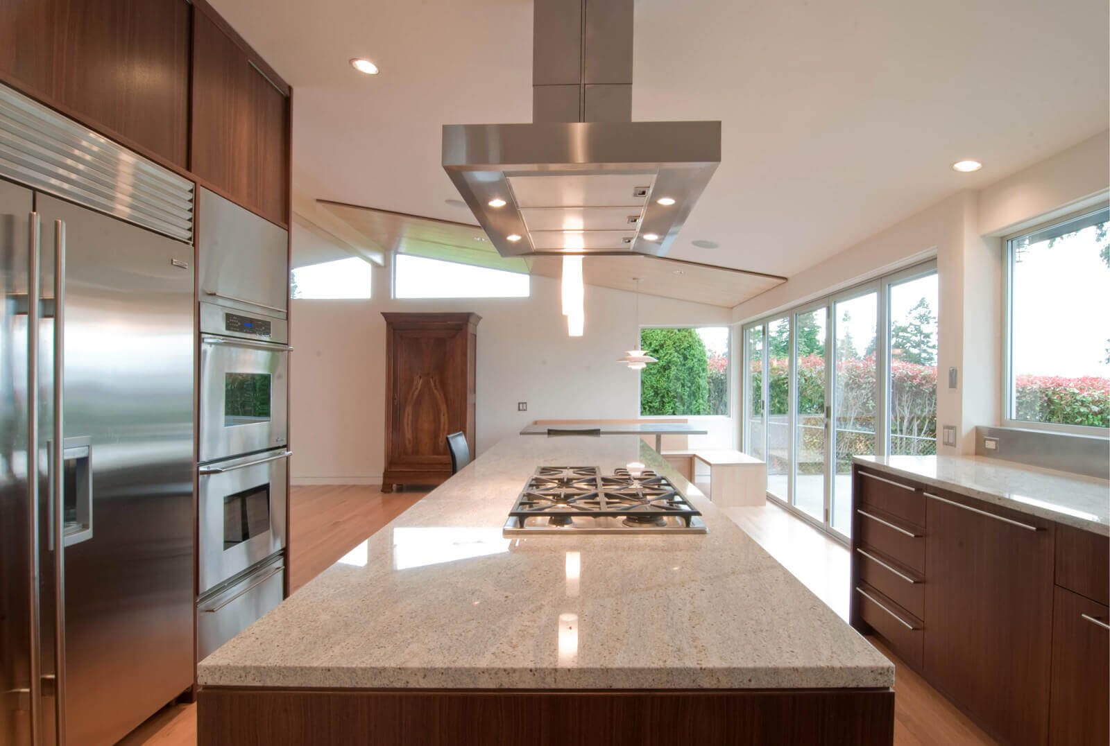 Like most contemporary kitchen designs, this room makes the modern kitchen island with cooktop the focus of the space. The marble countertops add softness to the warm tone of the space