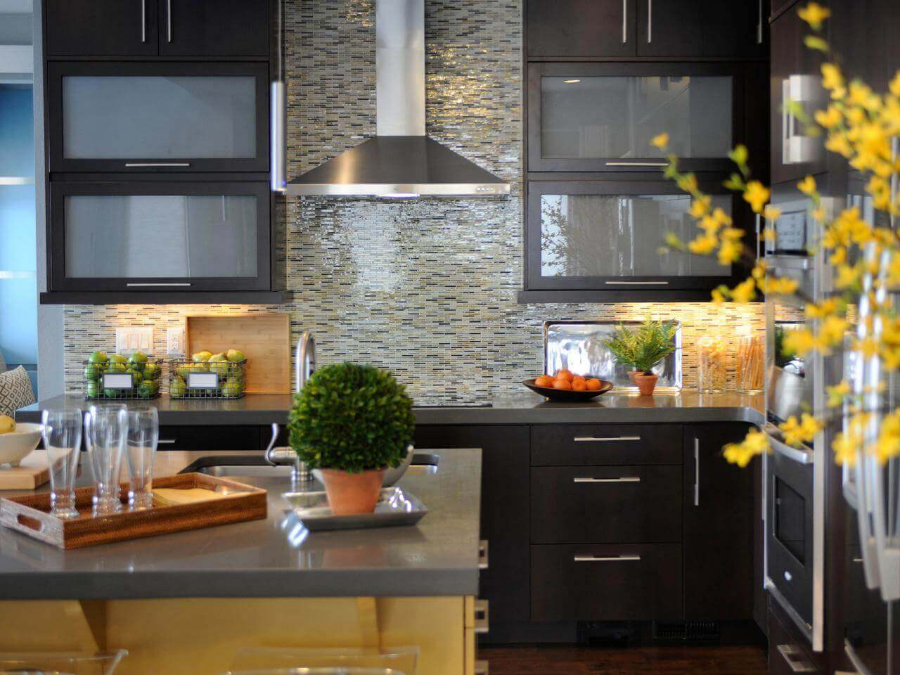 Exquisite mosaic modern kitchen tiles backsplash meld with stainless steel countertops while the dark brown wood cabinets and light brown island base add just the right amount of wood grain to accent the backdrop