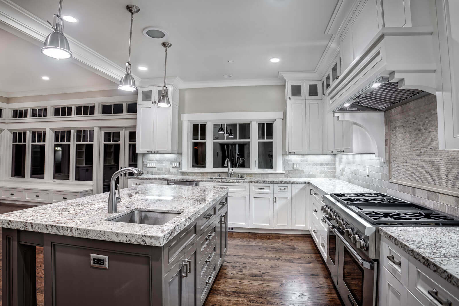 The crisp white backdrops and cabinets take up the larger feel this modern kitchen with granite countertops, but the use of the black–spotted gray granite countertops helps to keep the entire fixtures blended with the design