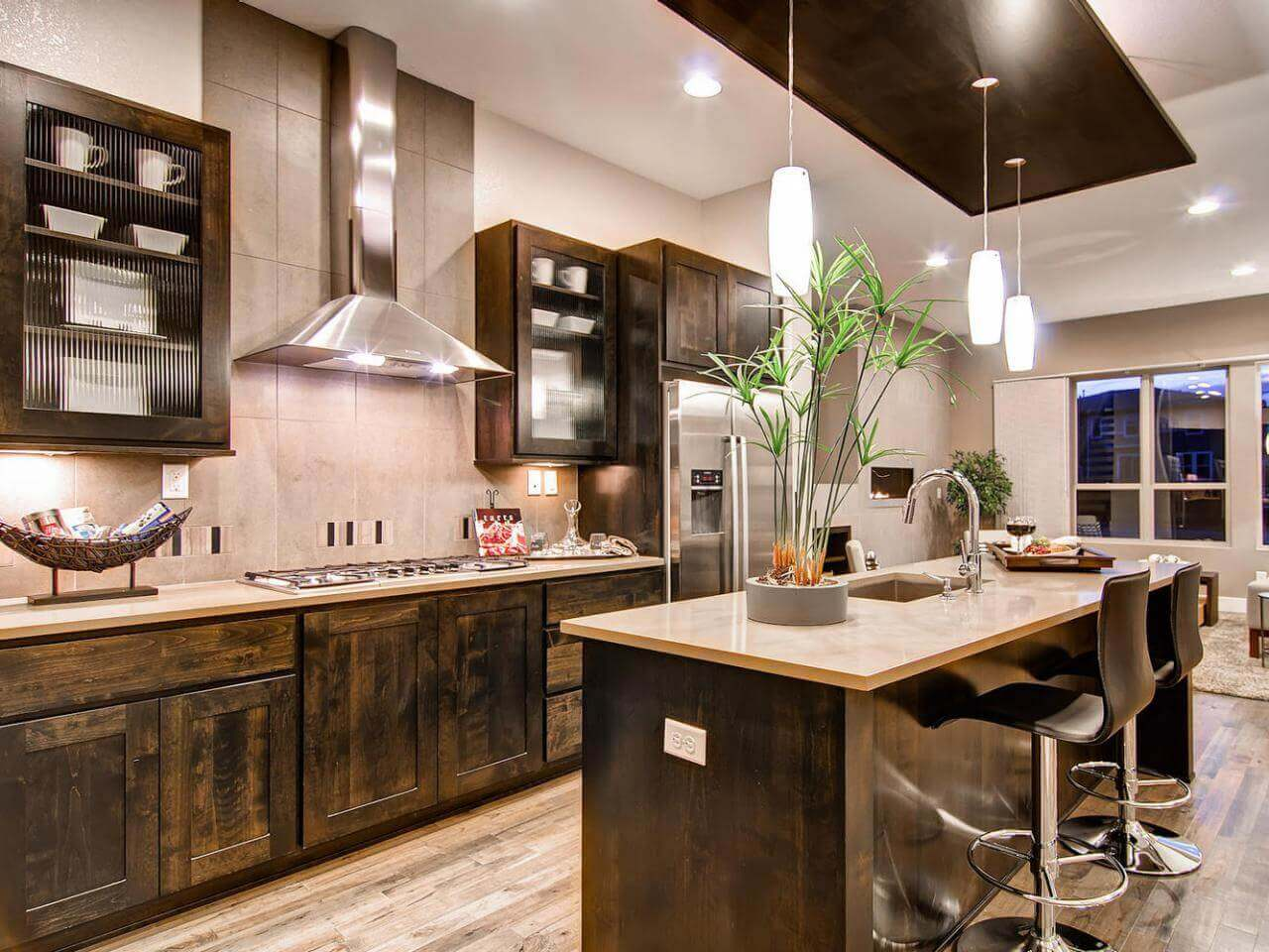 Faced with rustic multiple tone wood base, the island in this modern kitchen with rustic elements lend inspiration from the stain tone throughout the remainder of the room. Granite countertops on the lower cabinets finished in a shade of stain wood that pulls in elements of the outdoors inside