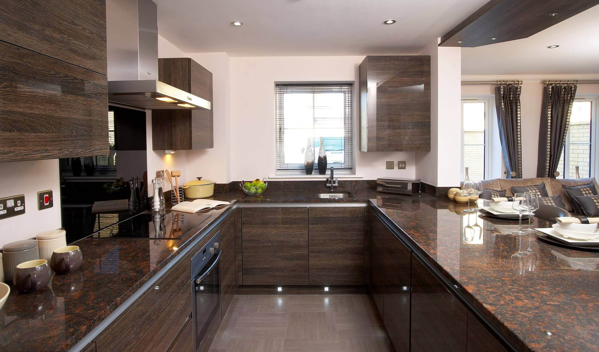 Dark wood cabinets throughout this modern u–shaped kitchen with island stand out in contrast from the ceiling and walls. The real eye catcher here however is the dark brown marble countertops that mesh unbelievably well with the cabinets
