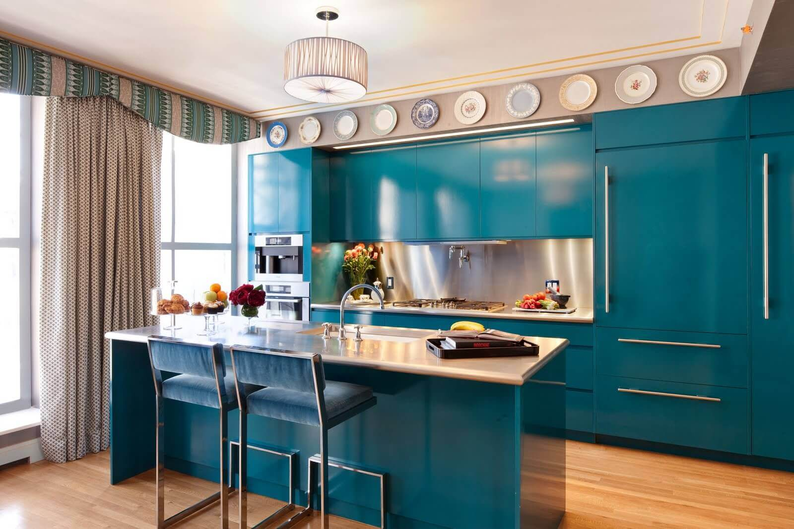 Contemporary blue kitchen cabinets, and blue bar stools give this kitchen a bright look and feel. The brown wooden floor anchors the otherwise light coloured room and a free standing blue island with granite block top adds extra workspace