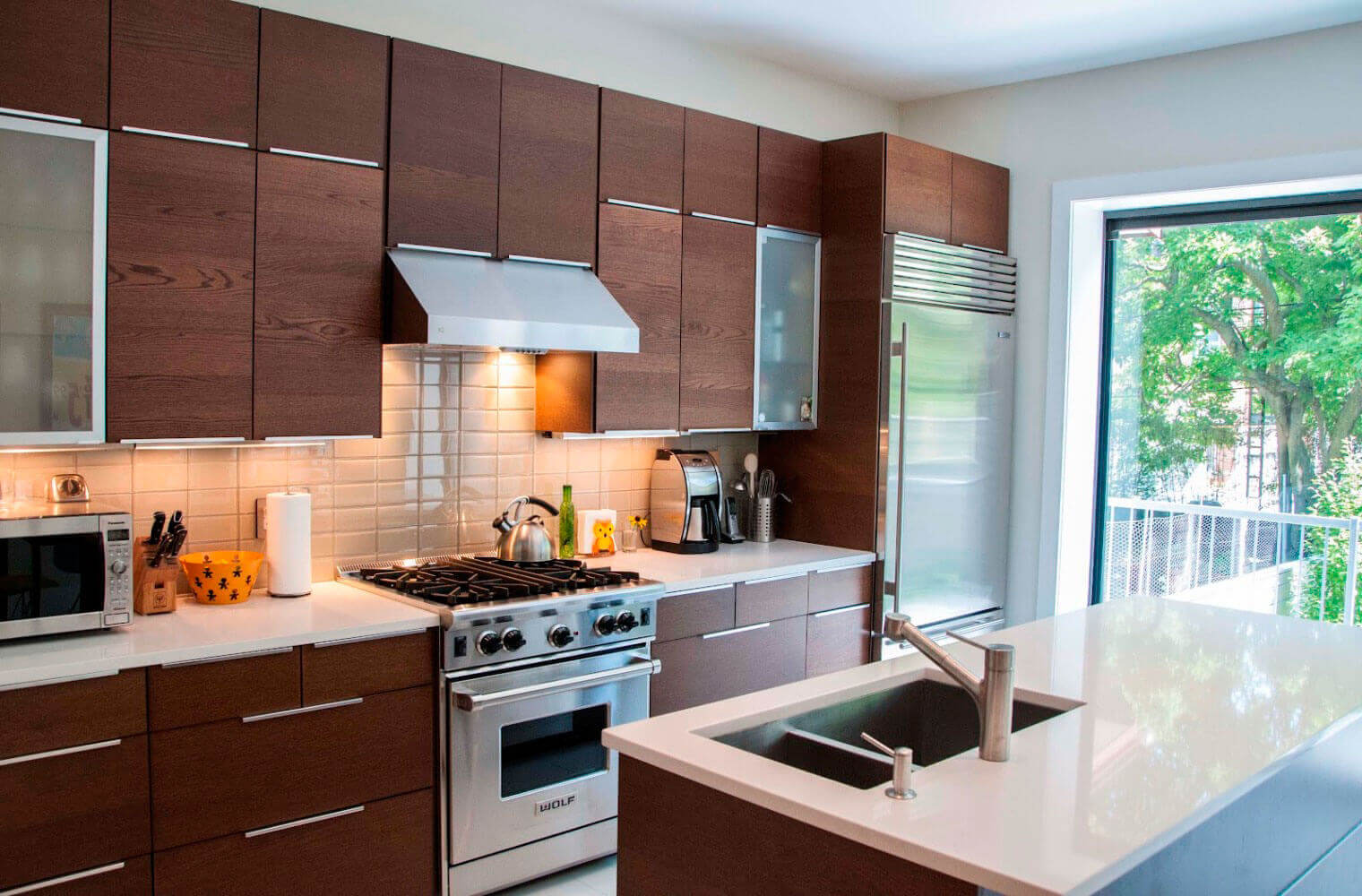 This kitchen has been completely transformed to a contemporary kitchen. Some of the key elements it features include sleek contemporary kitchen cabinets, brick backsplash, granite countertops, a custom island, stainless steel appliances, floor–to–ceiling windows, and industrial light fixtures