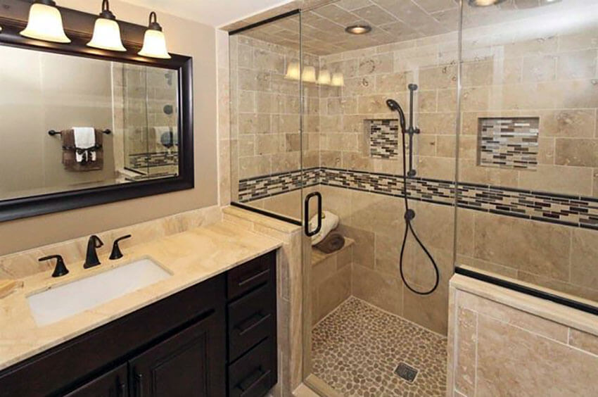 bathroom with travertine tile glass tile design and pebble rock floor