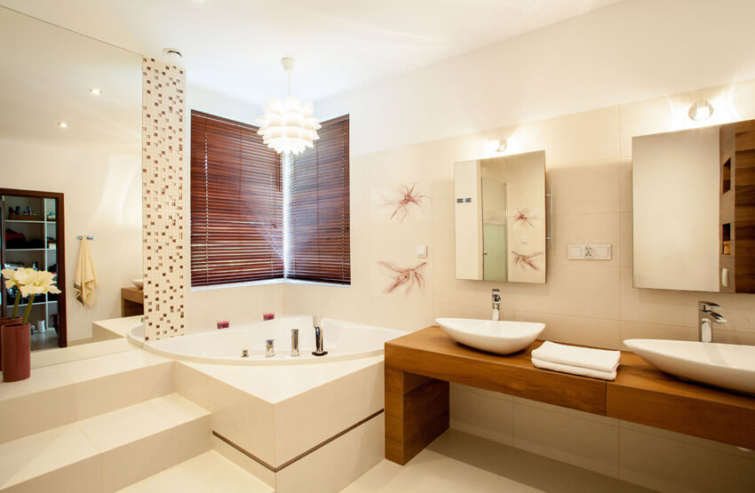 bathroom with tub and vessel sinks