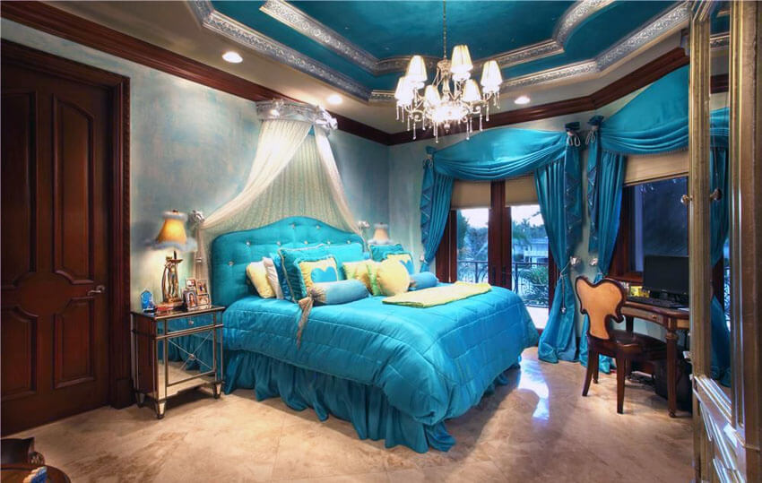 This beautiful teal bedroom with princess bed curtain and tray ceiling hangs a white pleated princess bed curtain hangs over a teal upholstered headboard with matching throw pillows and bedsheet. The teal and silver tray ceiling holds the hanging lamp chandelier that gives the room refinement and luxury