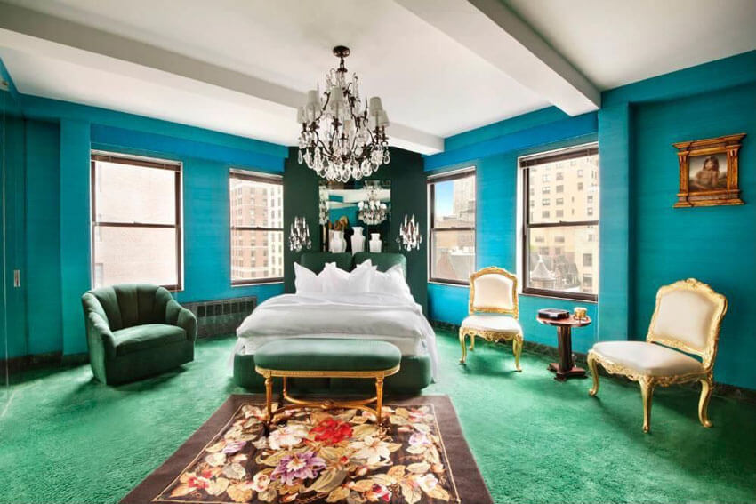 This modern style bedroom with teal walls chandelier and green carpet combines emerald and teal color to create a fancy space. It surrounds a small wooden coffee table on one side of the bed with gold framed, white upholstered royalty chairs