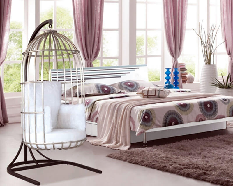 This bird cage swinging chair in bedroom incorporates stainless steel for a sturdy stand base, and white plush cushioning for seating. The chair offers the room a more interesting vibe and minimal modern feel