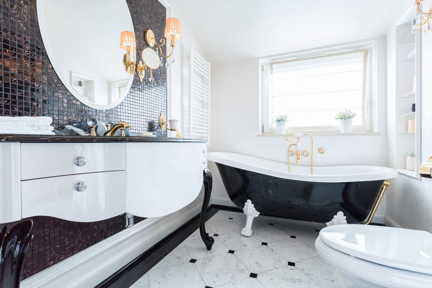 The black coral wall tiles, black granite cabinet, as well as gold finishes of the faucets and bathtub tap, all work together in this black white bathroom gold finishes to create a sleek modern bathroom design that would fit right in at any luxury apartment