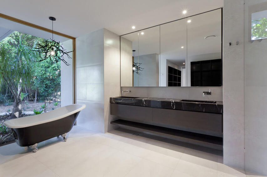 Nothing the lovers of nature will fancy like this black white style bathroom overlooking garden area. Resisting the grass, ferns, and flowers that bring a relaxing and fresh feel to the space will be difficult for the outdoors types