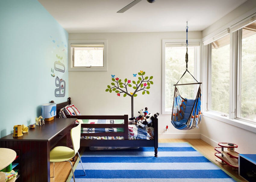 With large awning windows, this space with a blue hanging chair in kids room has terrific views of the outdoors. The light hardwood flooring and white walls are beautifully contrasted by a large striped area rug, and a pale blue accent wall