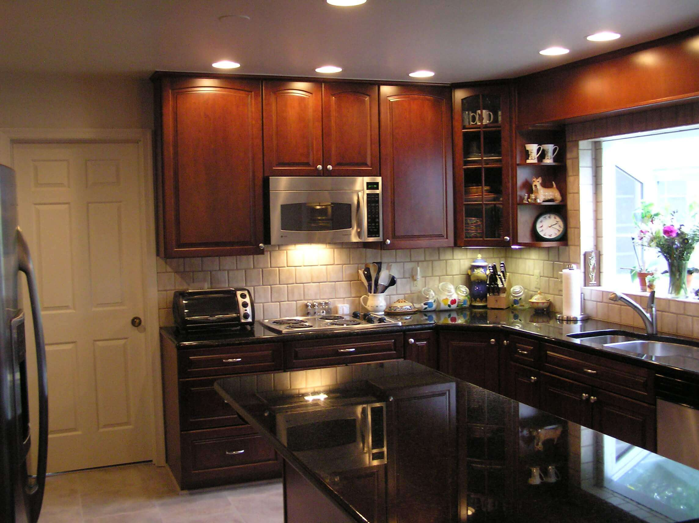 Budget friendly kitchen remodeling ideas can take a basic minimalist space and enhance it by the addition of simple elements. White brick–shaped backsplash in between the light brown upper and dark brown lower cabinets in an otherwise dark space balances out the look in this kitchen