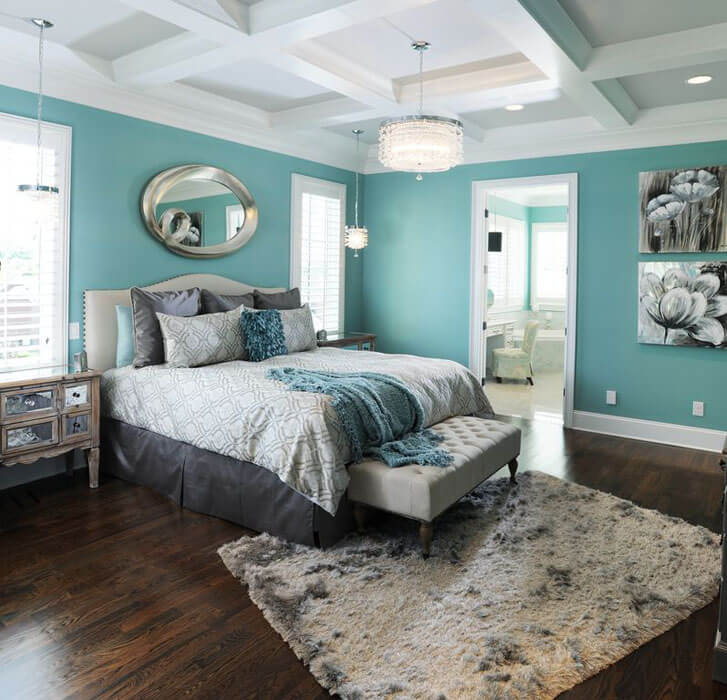 The subdued shade of teal in this contemporary bedroom teal walls mirror dressers wood flooring and shag drum pendant lights is enhanced by the heavy brown, grey, and beige accents in the room. The light grey throw rug that matches well with the upholstered bench gives color to the dark hardwood plank flooring