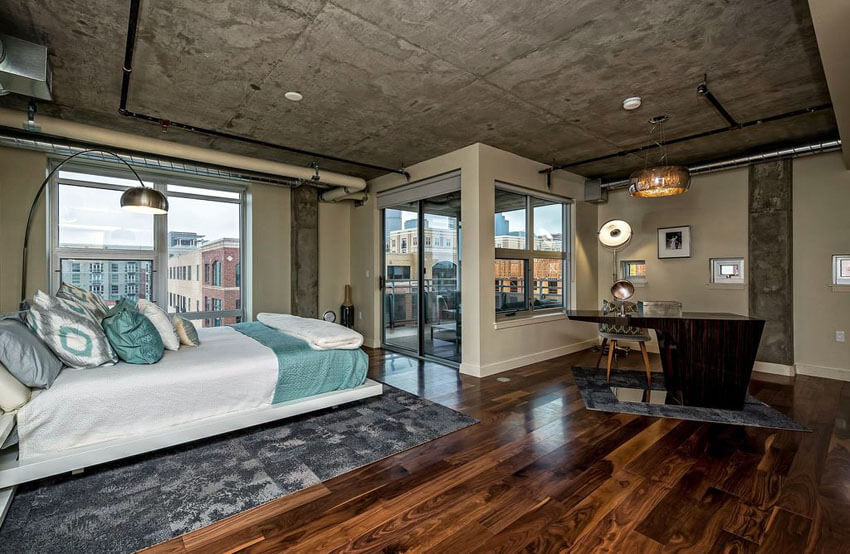 Contemporary Loft Bedroom with Balcony Wood Floors Concrete Ceiling and Exposed Duct Work
