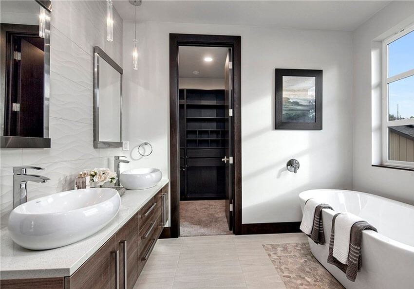 The hanging clear glass pendants at the vanity add a touch of glamor to this contemporary master bath with pendant lights. The glitzy lighting fixtures are a beautiful complement to this overly bright white bathroom