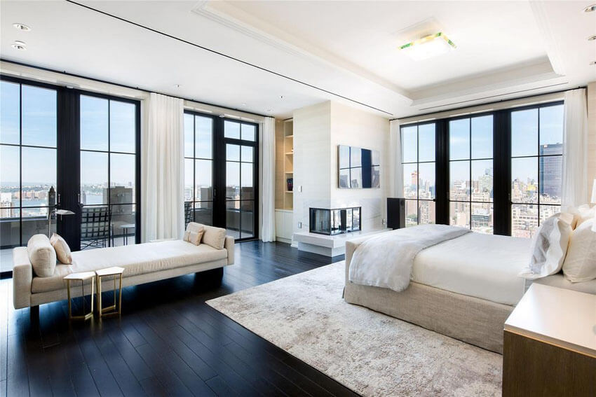This contemporary master bedroom with dark oak floors and city views features flooring surface in dark oak planks that is complemented by the surrounding floor–to–ceiling dark framed windows. The crisp white walls and ceiling balance out the feel
