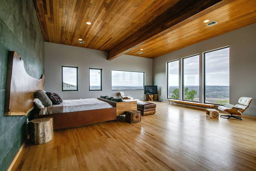 With warm oak wood ceiling strips and floor planks, the ceiling of this contemporary master bedroom with oak wood floors and ceiling is a perfect reflection of the floors. The warmth and grainy texture of the wood provides an impressive contrast to the grey walls
