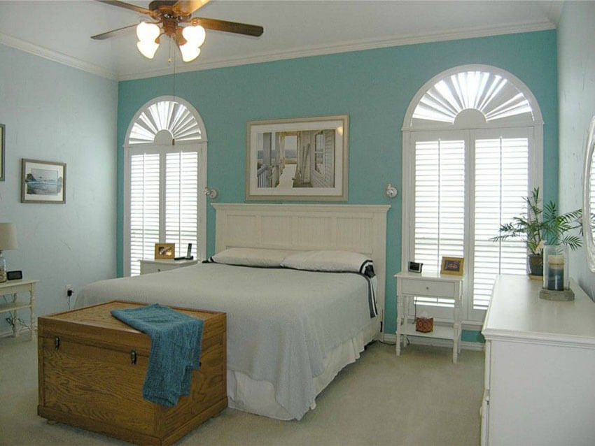 This cottage style bedroom with white and blue theme with curved decorative windows and plantation shutters obtains its cottage style feel from the curved windows and plantation shutters on both sides of the matching white headboard