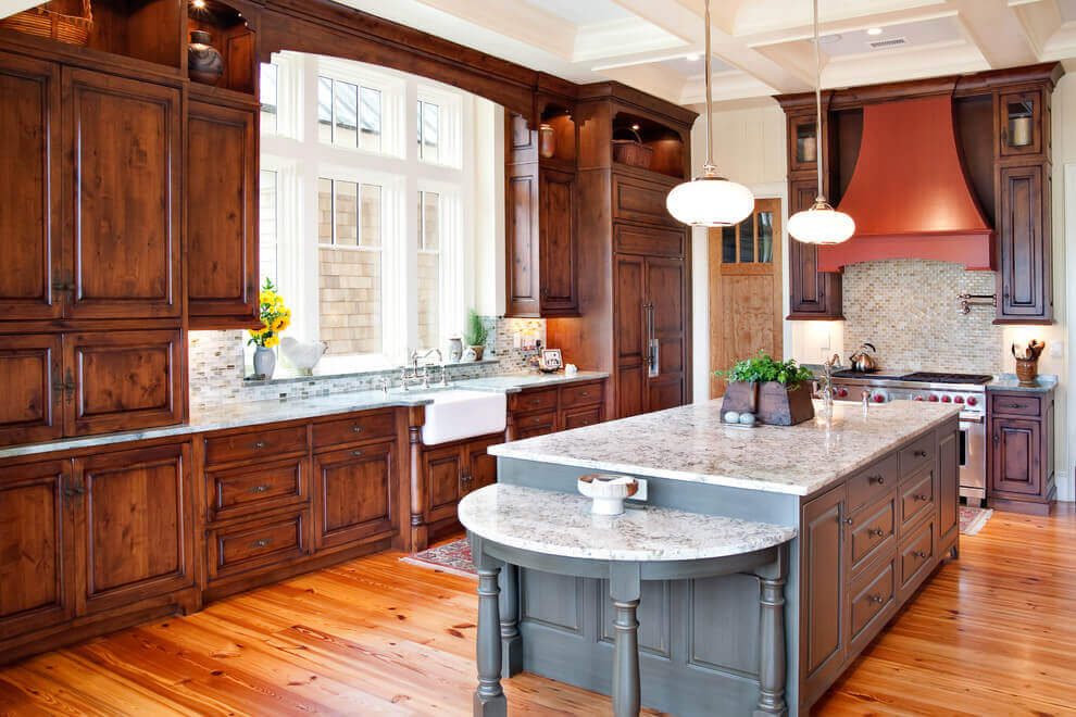 Medium brown hardwood cabinets line the entirety of this craftsman kitchen and a box–like shaped island carries the same wood material but in contrasting color. The warmth of this wood wonder is enhanced with marble countertops