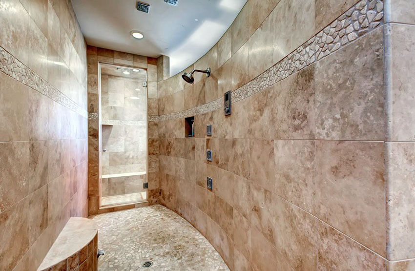 curved travertine shower with pebble floor tile and round bench
