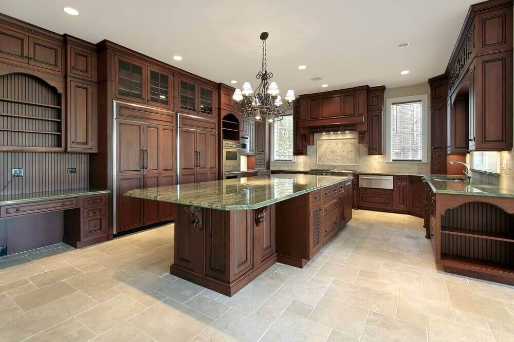 A luxurious dark wood kitchen design with a low level island for food preparation! The granite of the island top and countertops contrasts with the fine dark wood of the cabinets