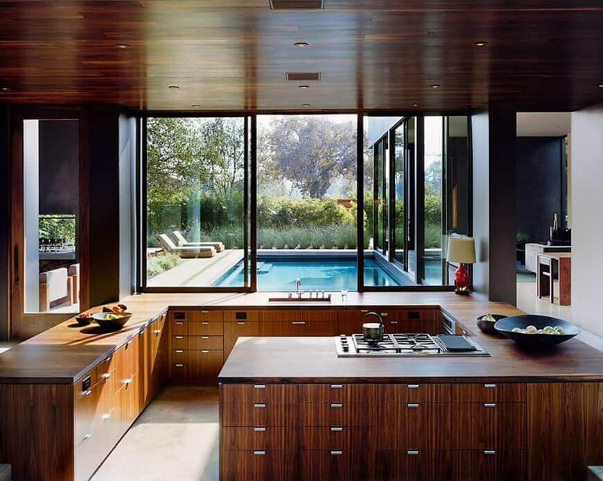 G–shaped kitchen design with stained dark wood ceiling and cabinets, porcelain tile flooring, and bowls of fruits strategically placed on the lower cabinets. The gorgeous pool view is enhanced by the full wide windows