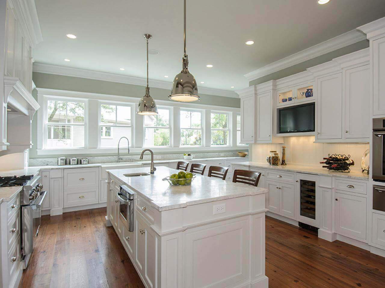 Crisp white kitchen with white walls, ceiling and cabinets! The white custom kitchen island at the center of the kitchen helps to draw the eye down to the wooden floor that balances out the feel of the entire space