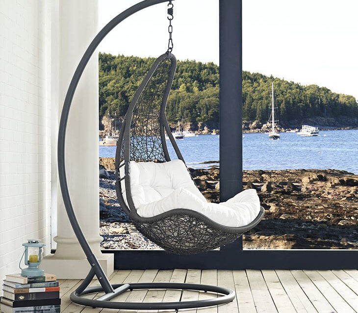 This nest style indoor swing chair on stand combines an all around abstract rattan pattern in black with a tufted seat cushion in white. Placed next to a large window, the chair exceptionally complements the outdoor natural lake shore scenery
