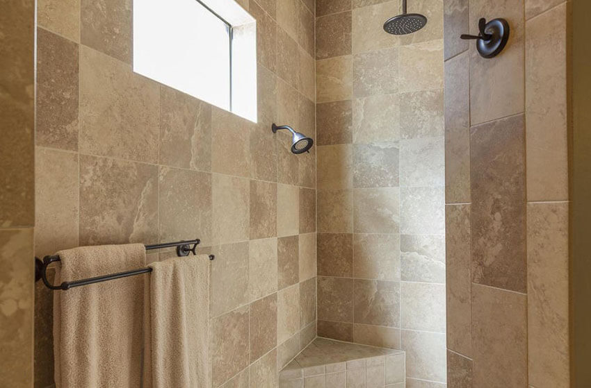 Inside A Travertine Shower With Rainfall Shower And Small Bench