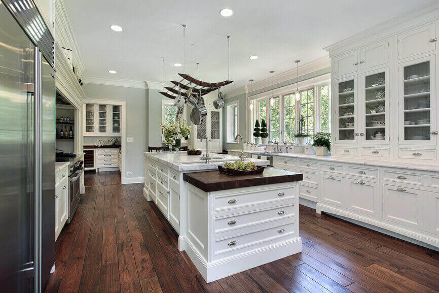 The smooth, clean white surface of this contemporary kitchen design is offset by the dark wood flooring fixtures. A two–tiered modern kitchen island features built–in cabinets to ensure efficient use of the space