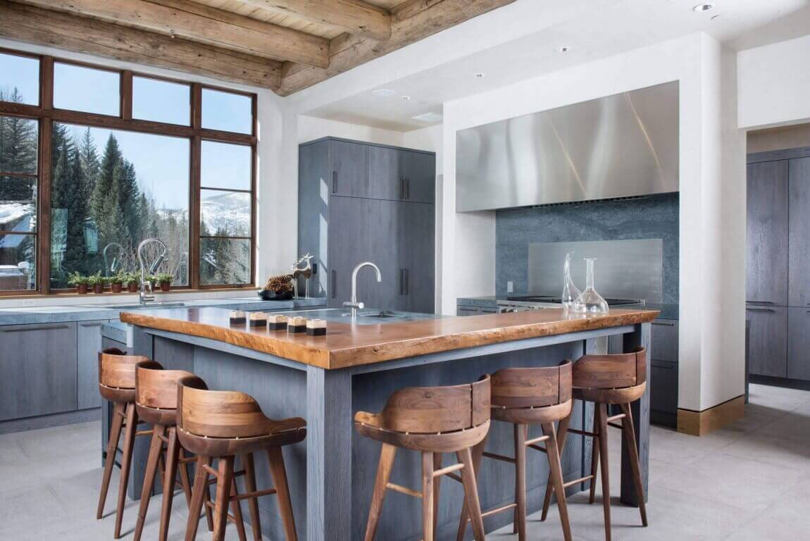 The sweet chocolate brown of the kitchen island top and window frame makes a stark contrast to the slick frosting texture of the gray kitchen island base, cabinets, and backsplash. The cork–like color and grain of the stool chairs accent the space and add a touch of rawness