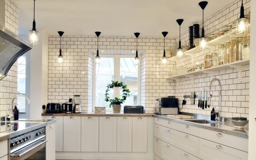 The crystalline pendant lighting fixtures bring attention to the brick–shaped white walls and backsplash as well as the glass rack above the functional countertop. The crisp white lower cabinets further accent the entirety feel of the space