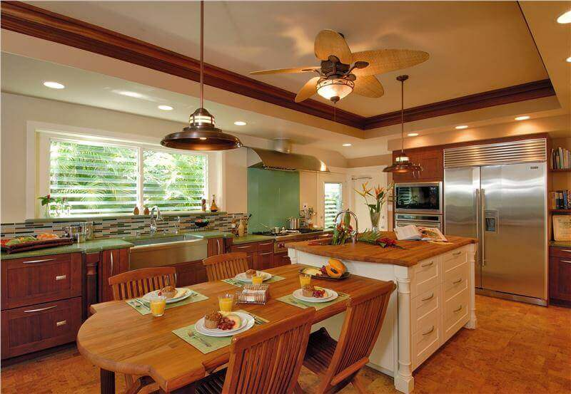The kitchen ceiling fan accents the warm brown tones of the room perfectly and adds to the natural look brought to the room by the cabinets and in–kitchen portion of the island