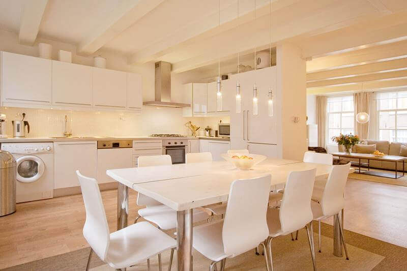 The stark white kitchen dining table go perfectly well with the entirety of the bright room. The white chairs mesh well with the dining table, kitchen cabinets as well as the white appliances
