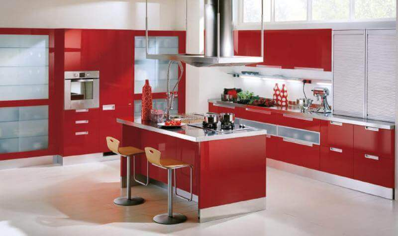 Bright shades are extending their acceptability to the indoor. As seen here, using red color on the cabinets and island adds a wonderful new dynamic to this kitchen space, especially against the white background