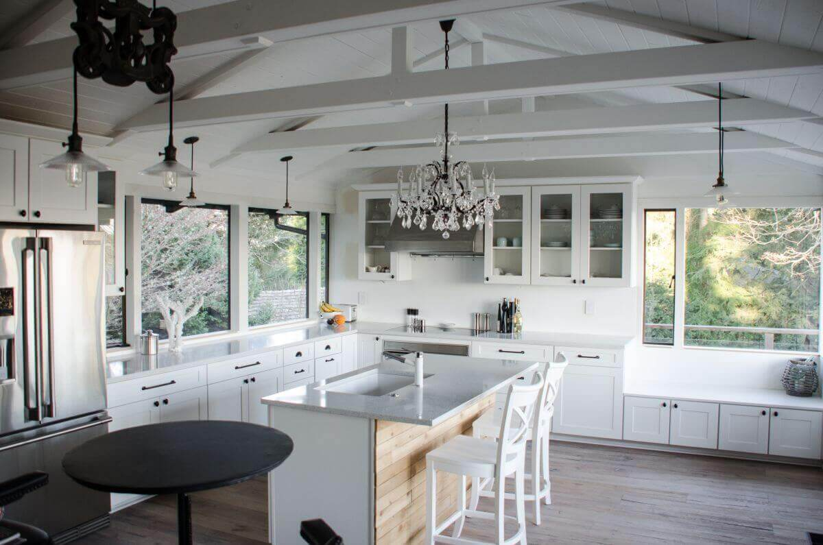 A large white kitchen in luxury home! It features a central island with sink, dark wood floors, white cabinet thus creating contrasting color scheme between the white kitchen design and the floor. The elevated white–vaulted ceiling adds to the design