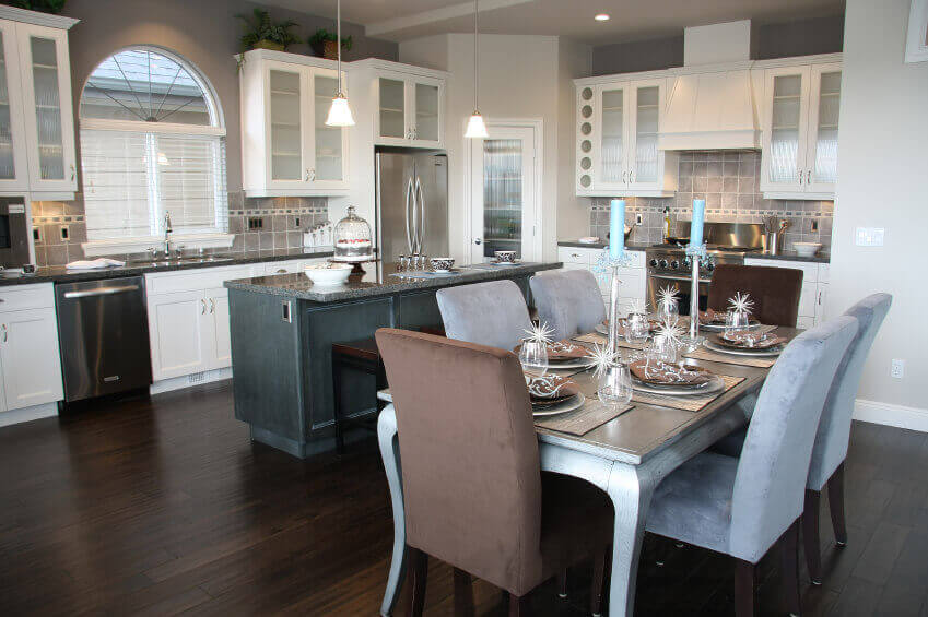 Here is a kitchen with dark wood floors. It features a decently sized island which does not hinder side–to–side movement, and a mini–dining that otherwise adds glamour to the entire space