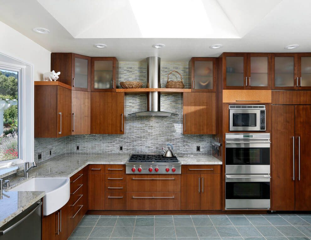 An elegant kitchen with double well ovens! The backsplash blends perfectly with hue of the floor tile as the medium brown cabinets and stainless steel appliances accent the bright feel of the kitchen