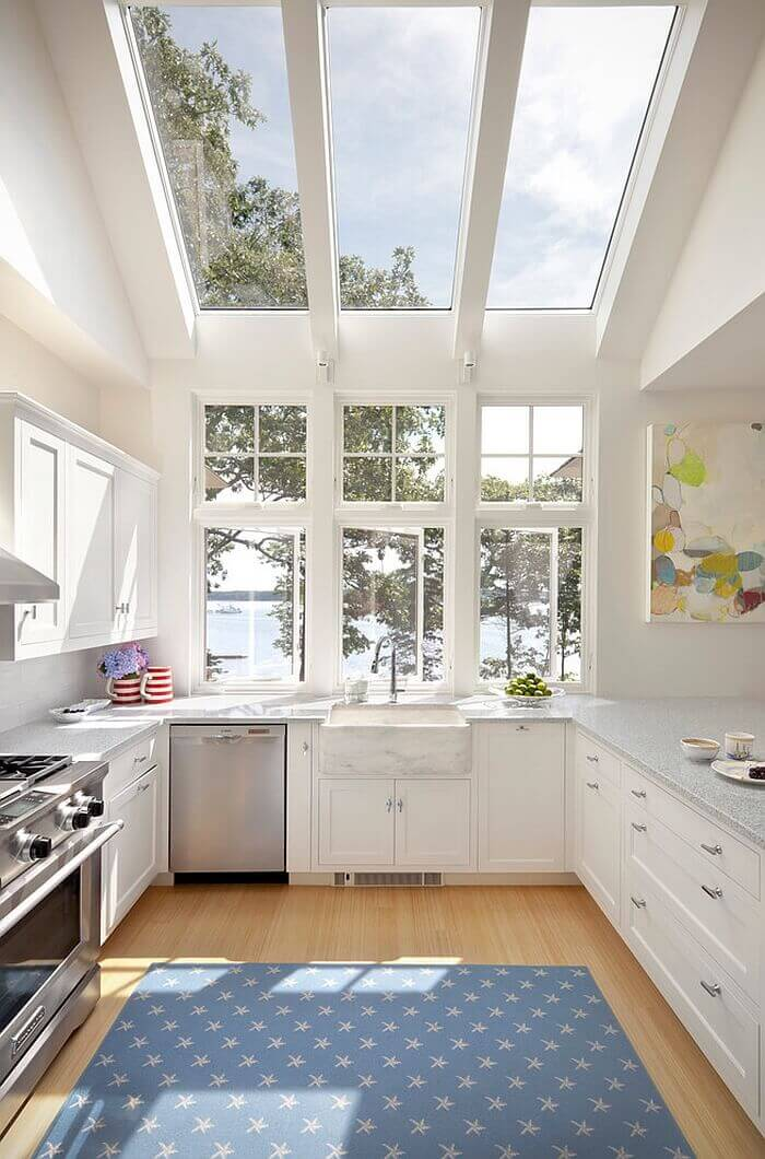 Three mid–sized windows let in natural light into this white kitchen with skylights and upon the granite countertop. The prominent skylights allow in that lovely light from above