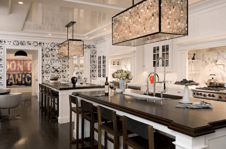 This kitchen with two islands brings in the stylings of a class with contemporary conveniences for an effortless function and luxurious look. Two luxurious chandeliers centered on each of the two islands balance the glowing tones of the flooring