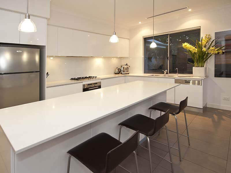 White L–shaped kitchen with fine wood white island and three contrasting black barstools. The white glass orb pendant lightings bring brightness to the work area and the flower vase on the countertop adds a little pops of color
