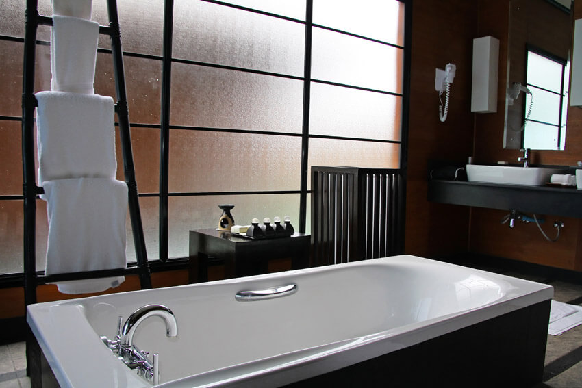 large bathtub with frosted privacy glass wall