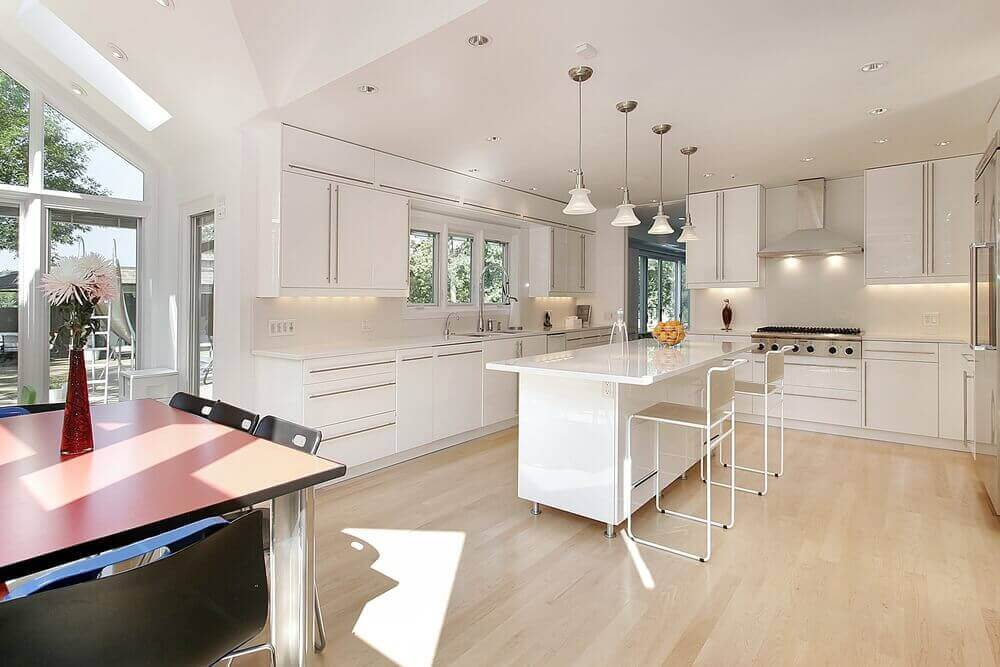 White, as the design scheme always gives freshness and new appearance. The ceiling tall window in this light wood kitchen design keeps light pouring through whole space. The wide wood flooring doesn't distract from the added detail