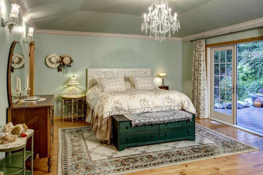 The knotty pine floors in this luxury bedroom with knotty pine floors and chandelier blend nicely with the persian patterned carpet, and duvet. The room derives its super eclectic feel from the low hanging chandelier, wall sconces, and lamp shades
