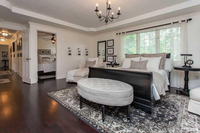 This luxury bedroom with maple hardwood floors and sleigh bed matches stark white ceiling and walls with dark toned maple hardwood floors. It features a central black metallic chandelier which gives the space a slightly classic feel