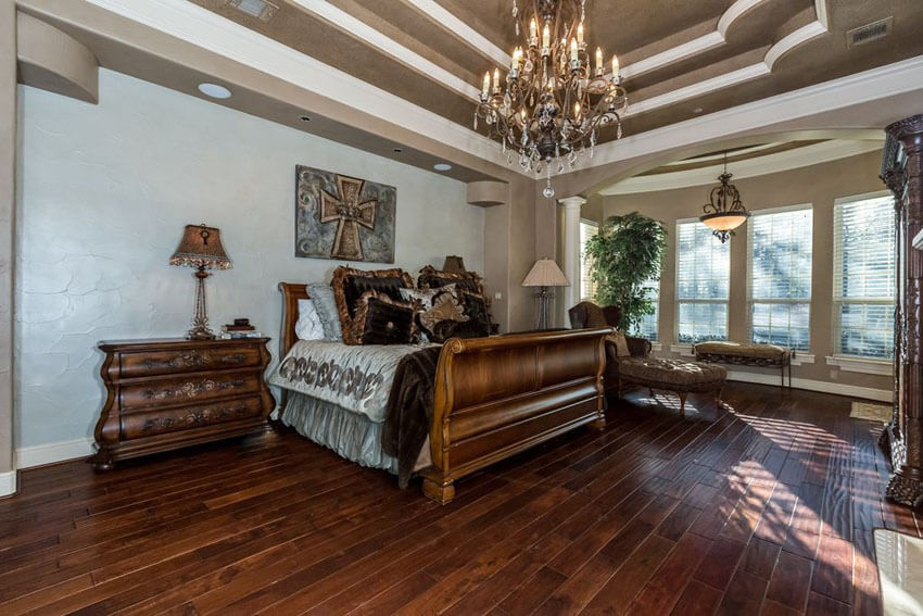 This luxury master bedroom with hickory hardwood floors chandelier and elegant furniture blends rusticity with luxury. The warmth and rich grainy texture of the hickory floors is a good contrast to the light grey walls
