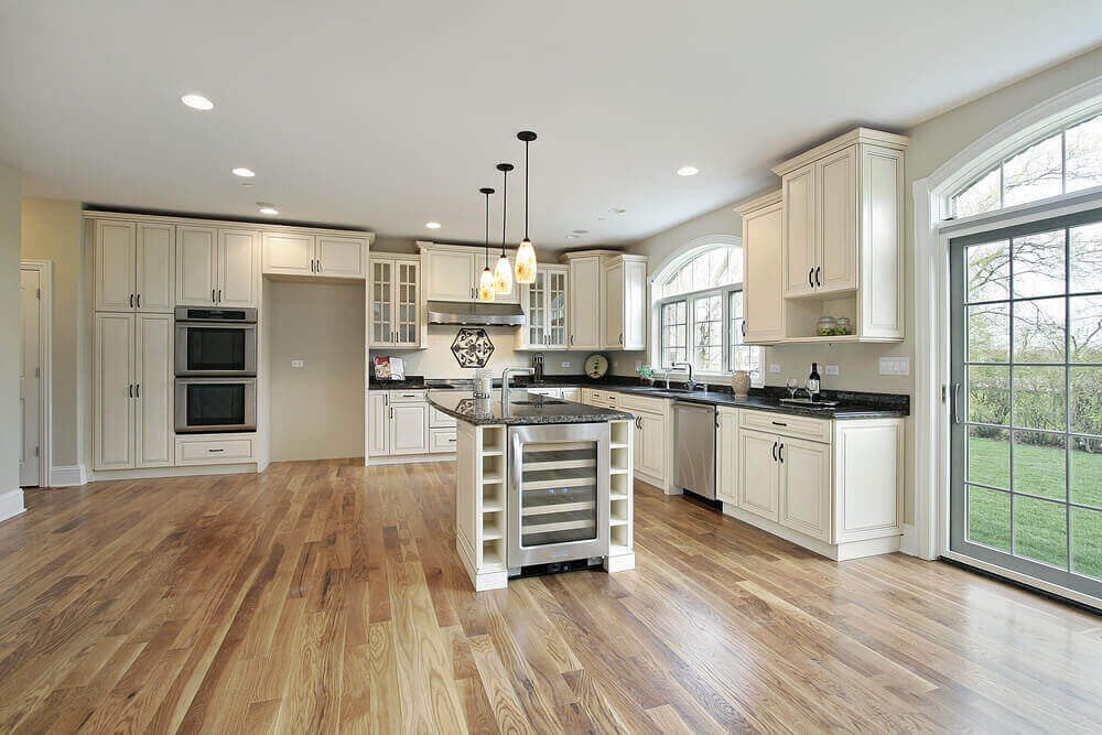 Stainless steel appliances and black granite countertops provide a definitive contrast in this massive custom kitchen design. The fine wood flooring draws eye to the expansive space available in the kitchen